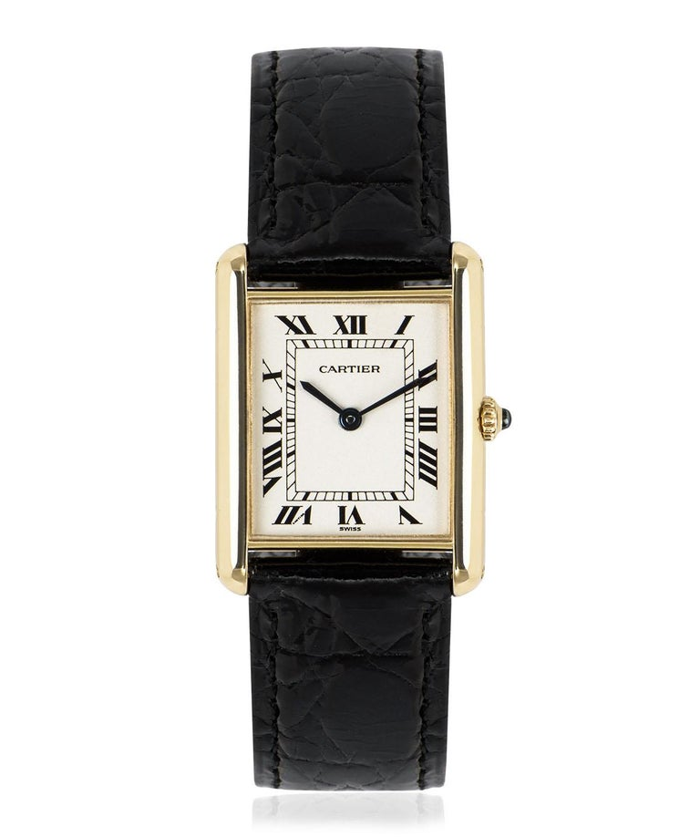 A 23 mm Tank Louis in yellow gold by Cartier. Features a silver dial with Roman numerals, sword-shaped hands in blued steel and a secret Cartier signature at V of VII. The crown is set with a single sapphire cabochon.  An original black leather