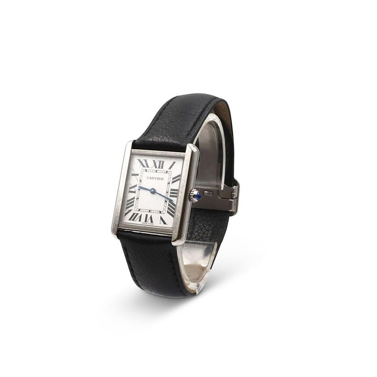 Authentic Cartier Tank Solo watch with steel case, beaded crown set with a synthetic cabochon-shaped spinel, silvered light opaline dial, Roman numeral hour markers, and blued-steel sword-shaped hands.  The black grained calfskin leather strap shows