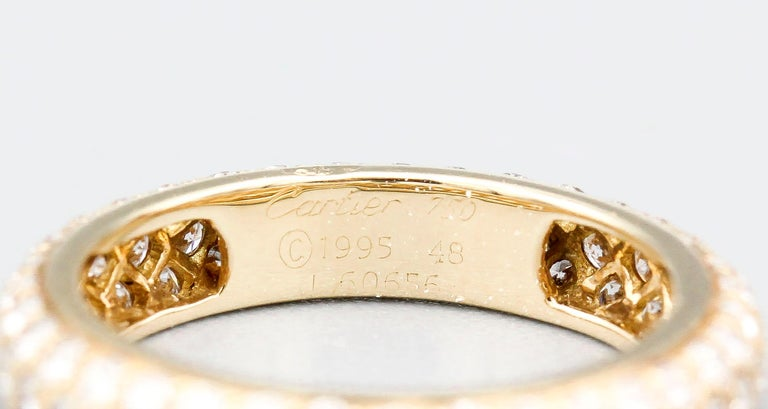 Elegant 3 row pave diamond and 18k yellow gold band by Cartier. It features high grade round brilliant cut diamonds in 3 rows. Approx. size 4.5-4.75 (European size 48)  Hallmarks: Cartier, 1995, 750, 48, reference numbers, maker's mark.
