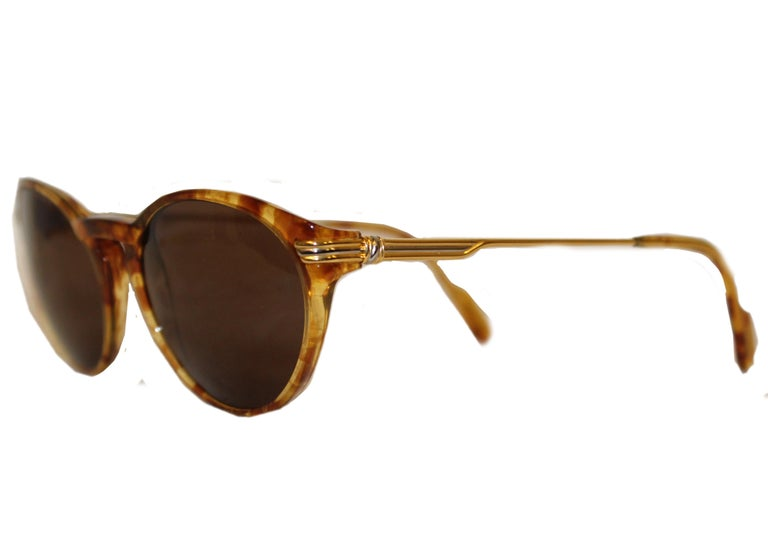 Cartier Cat Eye tortoise shell motif sunglasses with 135 mm temples and gold tone metal details on temples and hinges.  A Cartier logo plaque is featured at the end of each temple.   The Cartier work has stood the test of time and every woman, no
