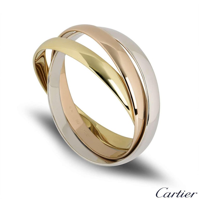 An iconic 18k tri-colour gold Cartier bangle from the Trinity de Cartier collection. The bracelet is made up of three intertwined 18k rose, white and yellow gold 9mm bands. The bracelet will fit a wrist size of up to 19cm and has a gross weight of