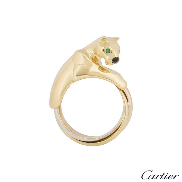 A beautiful 18k tri-colour gold panthere ring by Cartier from the Panthere collection. The ring is composed of a panthere head motif and is complemented with two round emeralds set as the eyes and onyx for the nose with the Trinity style body