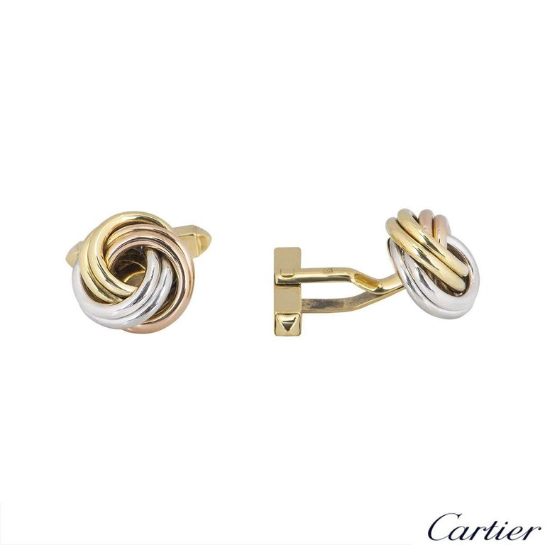 An 18k pair of tri-colour gold cufflinks by Cartier from the Trinity collection. The cufflinks are composed of a white, yellow and rose gold band interwoven into a large knot. The large knot measures 15.71mm in diameter with a classic hinged T-bar