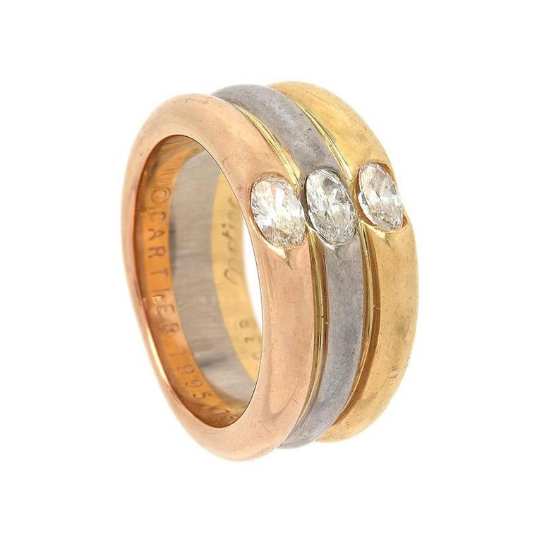 A 18k yellow, white and rosé gold Cartier trinity ring with three diamond ovals in the centre. The diamonds interestingly have a faint yellow, white and pink colour, matching the individual gold bands. The ring has an 18k gold stamp, 1995 year stamp