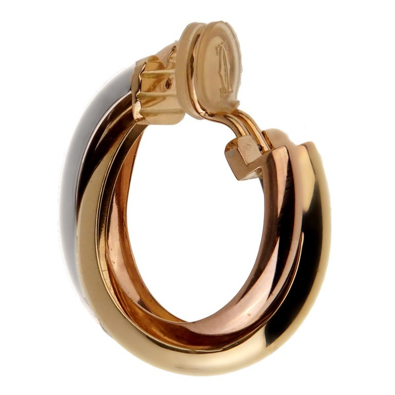 An iconic pair of Cartier Trinity Hoop earrings featuring white yellow and rose gold.