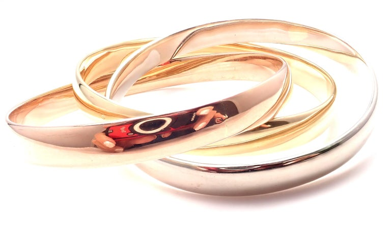 18k Tricolor Gold Large Model Trinity Bangle Bracelet by Cartier.  This bracelet comes with Cartier service paper and a box.  Details: Length: 7