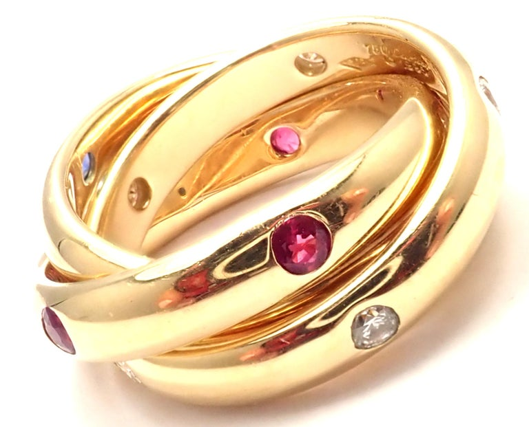 18k Yellow Gold Diamond Ruby Sapphire Trinity Band Ring by Cartier.  With 6 round brilliant cut diamonds VS1 clarity, G color total weight approx. .18ct 6 rubies & 6 sapphires Details:  Size: European 49 US 4 3/4 Width: Single Band Width: 4mm; Total