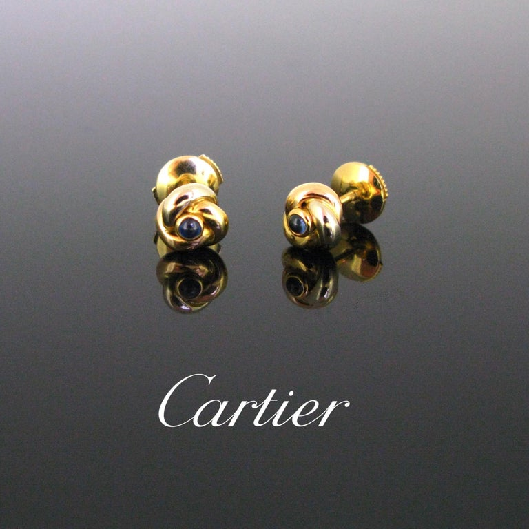 This pretty pair of earrings by Cartier is from the famous Trinity collection. The earrings are made in 18kt gold - white, yellow and rose. They are set with a blue sapphire cabochon in the centre. The earrings come in their original Cartier