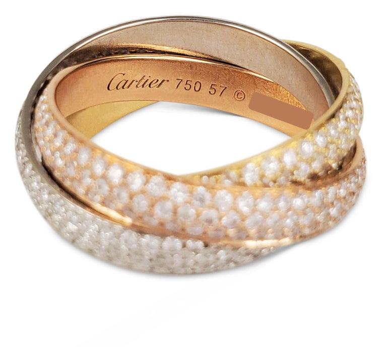 Authentic Cartier 'Trinity' ring comprised of three interlocking mobile bands of 18 karat yellow, rose, and white gold. Each ring is encrusted with pave set high quality round brilliant cut diamonds of an estimated 2.98 carats. Signed Cartier, 750,