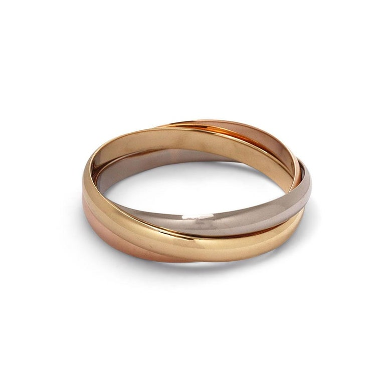 Authentic Cartier Trinity rolling bracelet crafted in 18 karat white, yellow, and rose gold. Each ring measures 8.5mm in width. Bracelet will fit up to size 7 1/2 comfortably. Stamped 750, Cartier, with serial number and import marks. Accompanied by