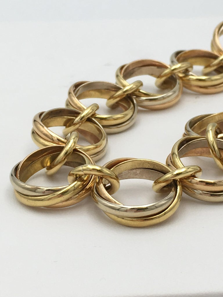 Authentic Cartier 'Trinity' link bracelet comprised of interlocking rings of 18 karat yellow, rose, and white gold. Signed Cartier, 750, Cartier 1991, with serial number. The bracelet measures 7 3/4 inches in length. Not presented with original box