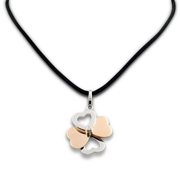 Authentic Cartier pendant crafted in 18 karat rose and white gold features four mobile heart-shaped discs set with two round brilliant cut diamonds weighing an estimated 0.12-carat total weight. The pendant hangs from a black satin cord. Signed