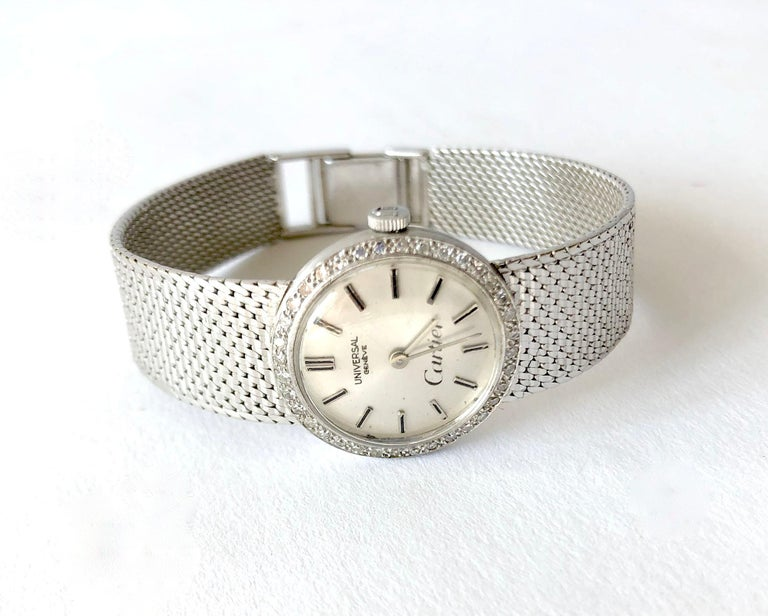 18K white gold mesh ladies Universal Genéve wrist watch with diamond surrounded dial by Cartier.  White gold mesh bracelet is made for a small wrist and measures 6 1/8