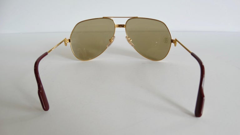 Snag yourself the ultimate pair of vintage sunnies! Circa 1983-1997, these Cartier aviator sunglasses are famously known as the Vendome Louis, are mixed silver/gold plated and feature brown tinted lenses with the Cartier logo engraved. Arms include