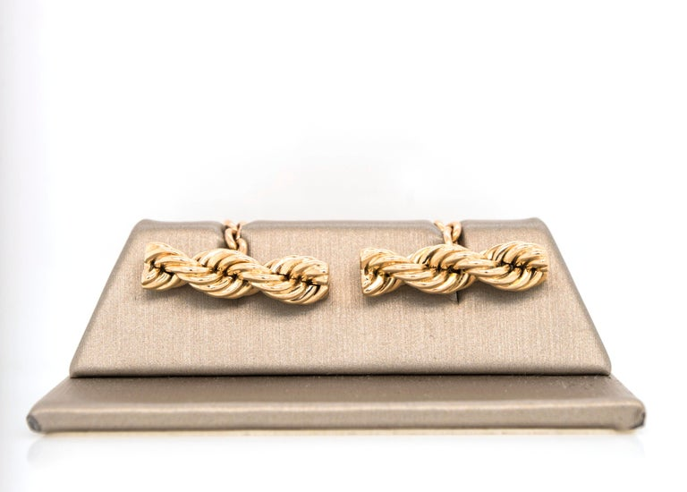 Iconic Twisted Rope Chain by Cartier.  Simple and elegant, these twisted rope cufflinks in 14k yellow gold will elevate your style any day of the week. Chain link closure. Very good condition. Signed