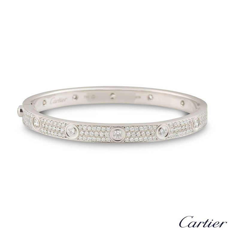 An exquisite 18k white gold Cartier diamond bracelet from the Love collection. The bracelet has 10 round brilliant cut diamonds around the outer edge in a rubover setting with 206 round brilliant cut diamonds pave set between each larger diamond.