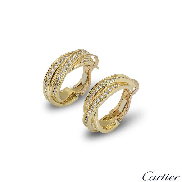 A sparkly pair of 18k yellow gold Cartier diamond hoop earrings from the Trinity de Cartier collection. The earrings comprise of 3 intertwined yellow gold bands with round brilliant cut diamonds pave set throughout. The diamonds have a total weight