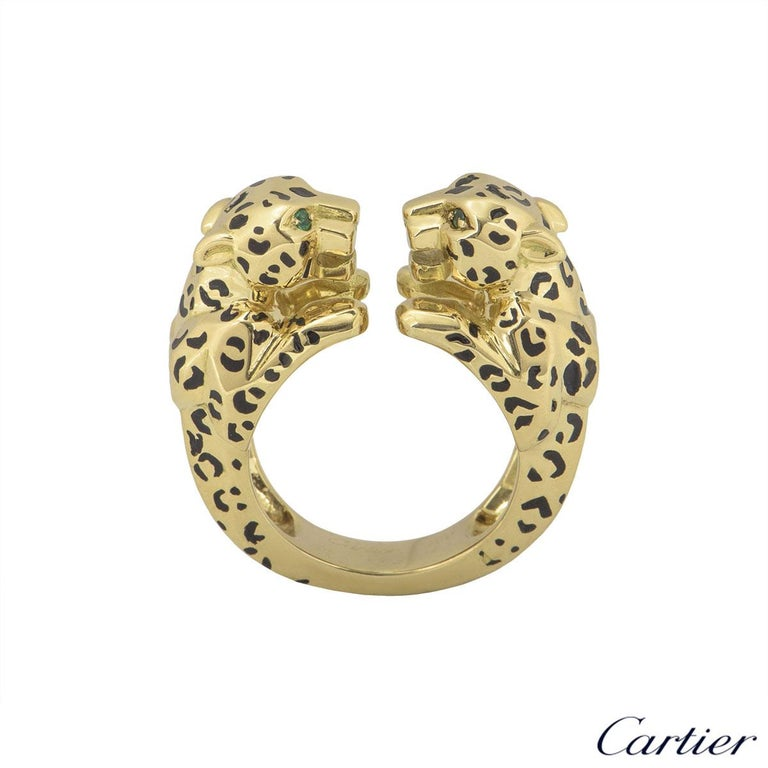 A beautiful 18k yellow gold and enamel ring by Cartier from the Panthere De Cartier collection. The ring is composed of two panthere head motifs beside each other set with bold enamel spots and are complemented with two round emeralds set as the