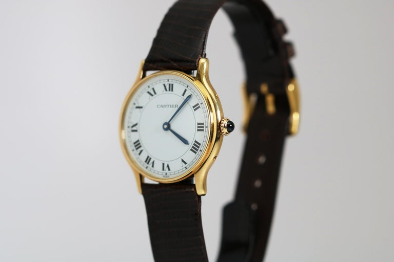 Brand: Cartier Paris Model/Ref: Dress Movement: Cartier Manual Wind 17-Jewels Case: 18k Yellow Gold Dial: White with Roman Numerals Stamped Paris Dimensions: 30mm Band: Brown Lizard made in Italy Lug Width: 16mm Year: 1980s Box/Papers: No