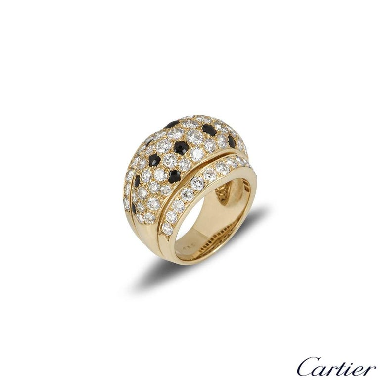 A beautiful 18k yellow gold dress ring from the Nigeria collection by Cartier. The domed ring is set with round brilliant cut diamonds with onyx scattered throughout. The diamonds have a total carat weight of approximately 2.38ct. The ring measures