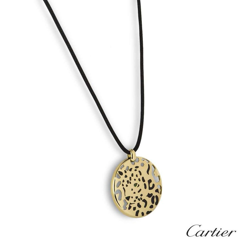 A stunning 18k yellow gold Cartier necklace from the Panthere collection. The necklace features a circular motif with a panther in the centre shaped from black lacquer, complete with a single tsavorite garnet as the eye. The circular motif measures