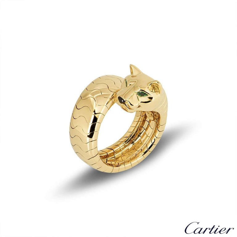 An 18k yellow gold ring from the Panthere collection by Cartier. The ring comprises of a Panthere head motif, set with tsavorite eyes and onyx nose. The body of the Panthere wraps around to form the band of the ring, measuring approximately 8mm in