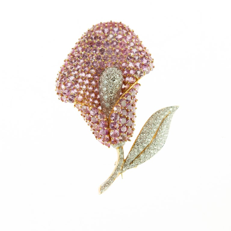 Magnificent sparkling Cartridge flower-shaped brooch embellished with 16.74 carat pink sapphires consist of a myriad of smaller precious stones (186 pieces). The pink petals create a delicate form enhanced by 3.63 (121 pieces) carat diamonds in a