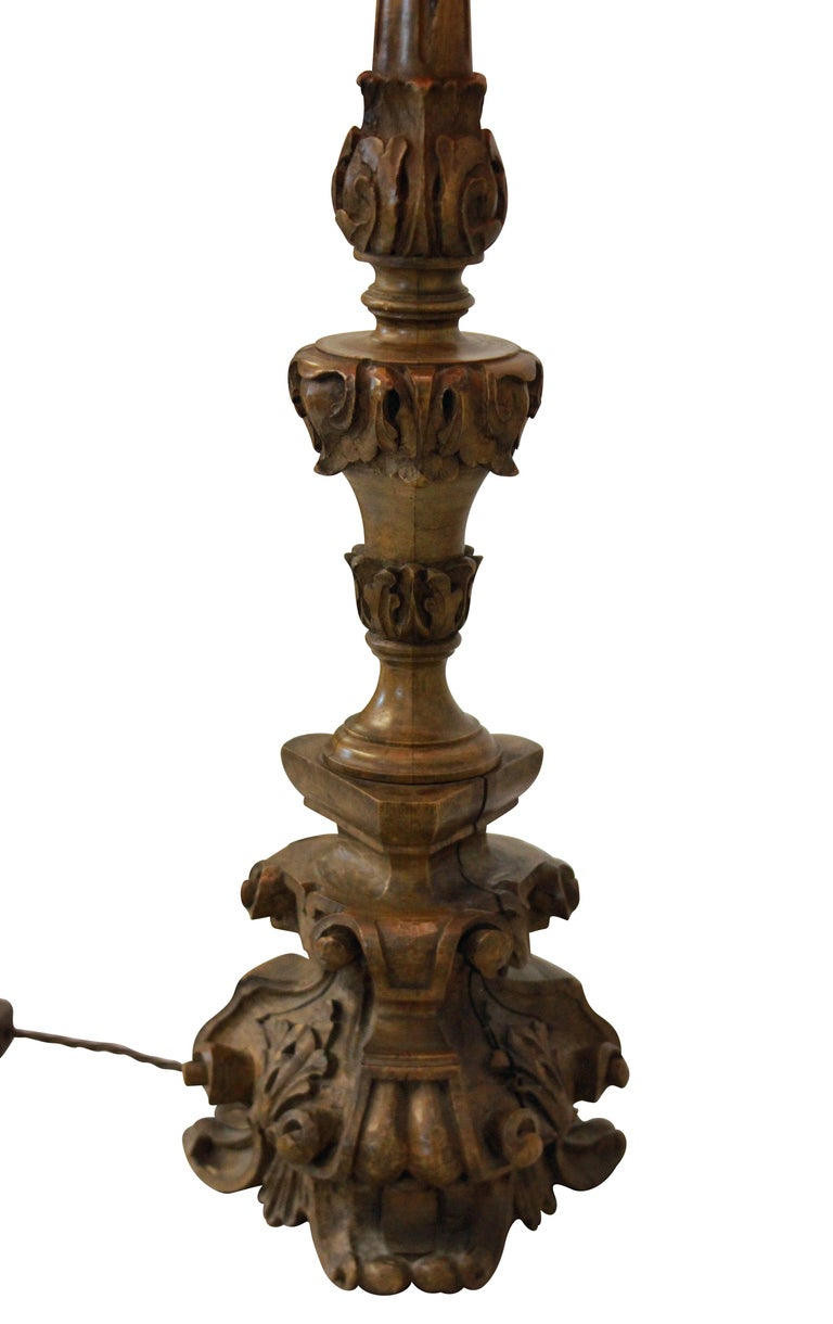 An Italian 18th century carved walnut pricket stick converted into a table lamp.