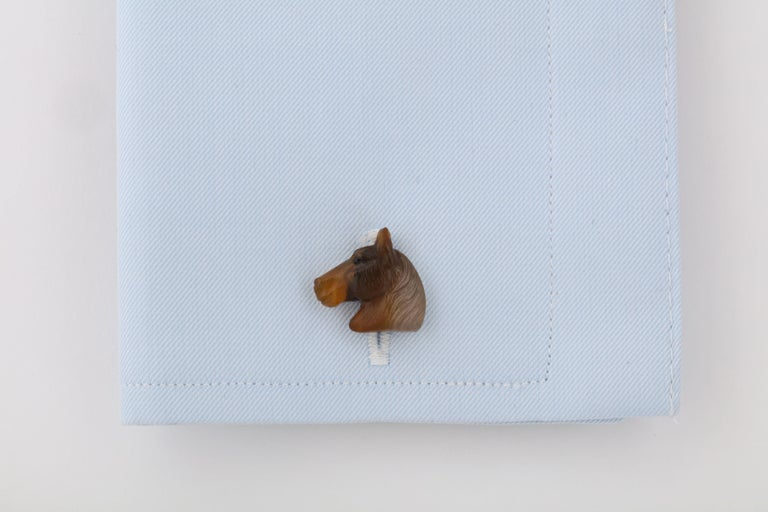 Beautifully, and realistically, carved from a single piece of brown agate, these wonderful horses are classic and timeless.  They are expertly mounted in 18kt white gold and feature a hinged mechanism and a horse bit on the back.  For the elegant