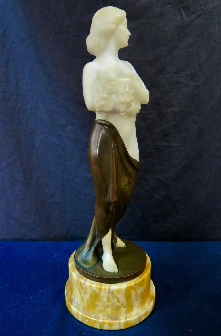 This vintage patinated bronze & hand carved alabaster figural sculpture dates from the early 20th century. The sculpture depicts a shapely semi nude young woman in a draped skirt descending from her hip. She modestly conceals her breasts by holding