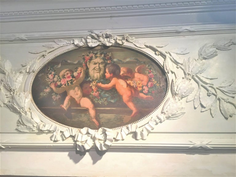 The architectural frieze fragment removed from panelling. The neoclassical styled panel with leaf garland intertwined with ribbon surrounding a colorful oil inset of four cherubs or putti dancing merrily with ribbon and floral garlands, probably an