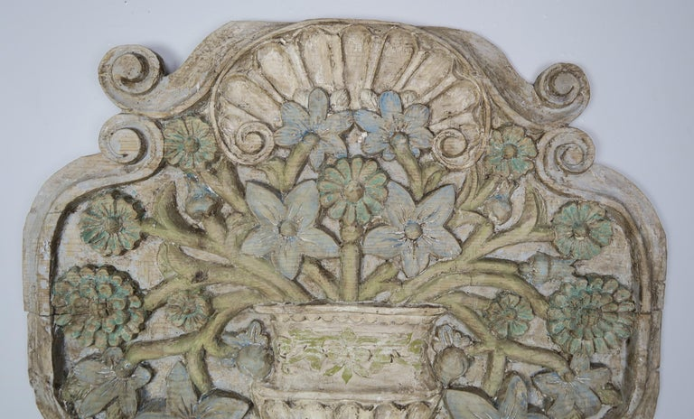 Carved wood and painted floral wall hanging depicting a beautiful carved urn adorned with flowers throughout.