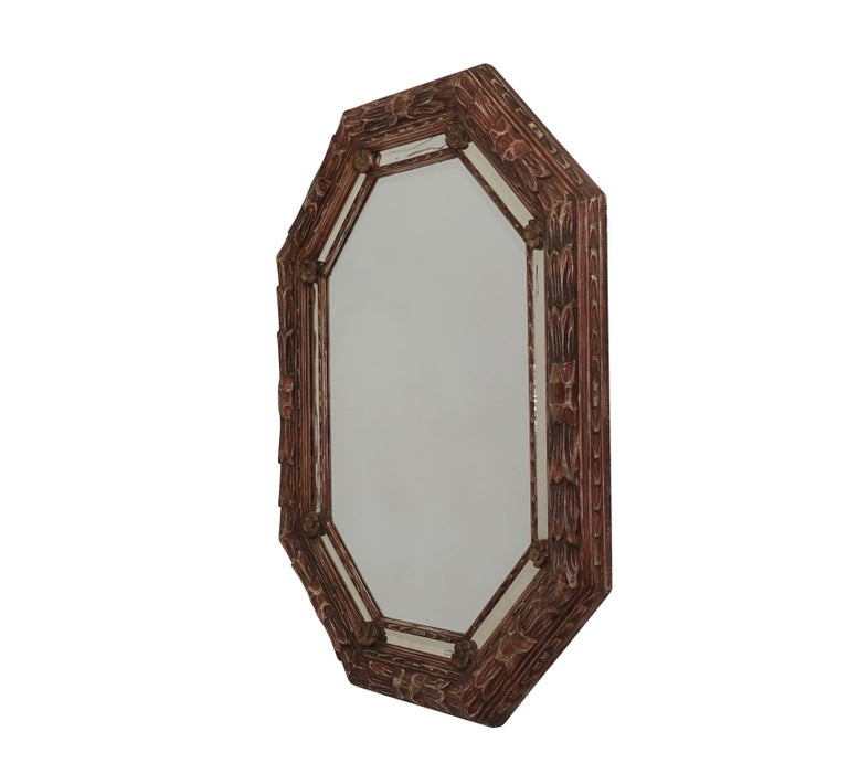 Octagonal shape leaf carved bullnose framed mirror with rosettes, having a red and white painted finish. The vintage mirror shows age and some clouding, Continental, mid-20th century.