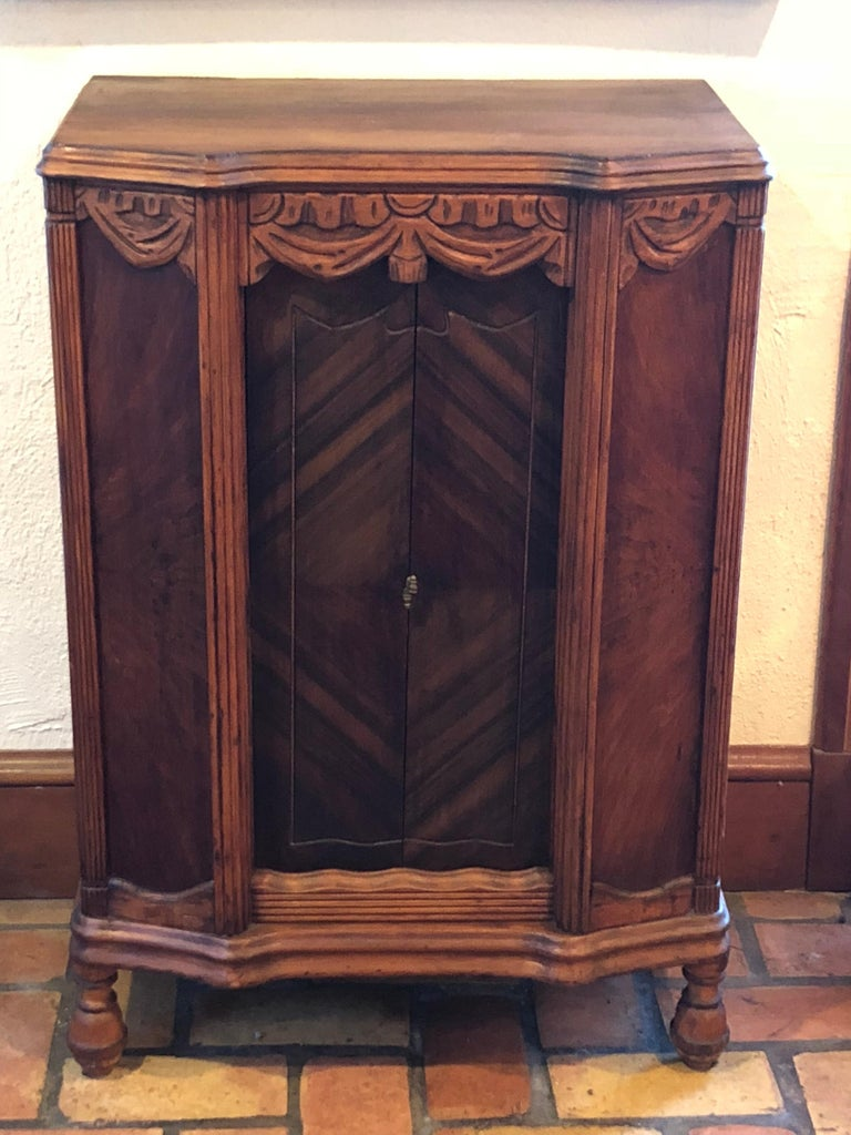 Carved antique wooden cabinet or bookcase. Great as a liquor cabinet as well or entryway piece with a mirror above it. The carved top is like a proscenium of a theater and the curtains part and open up to expose two shelves.