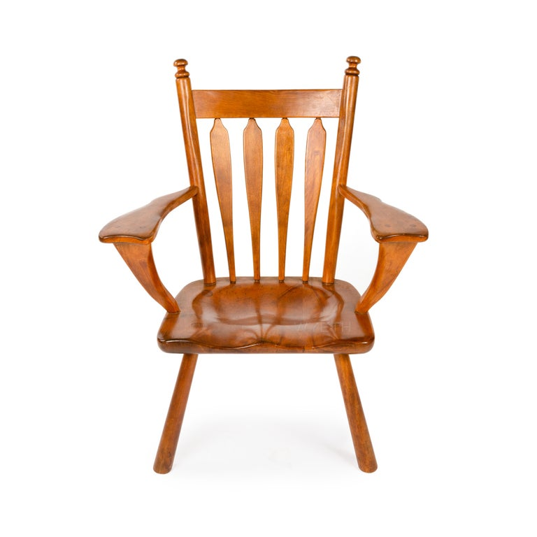 An armchair in solid yellow birch with a carved seat, splayed legs, hand-hewn spindles and wide uniquely shaped tapered arms.
