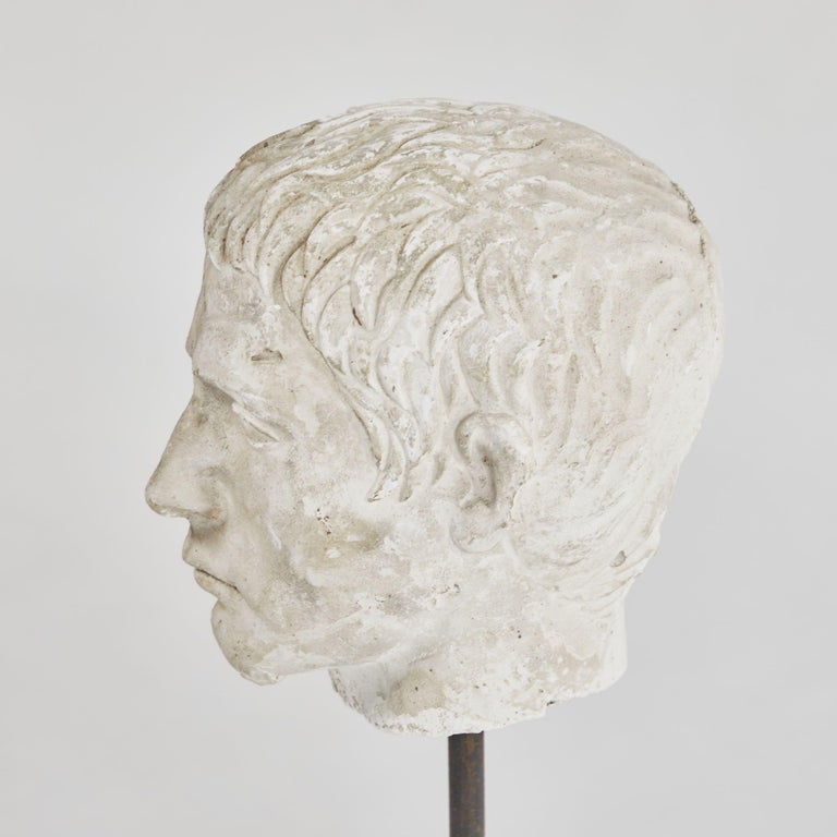 A carved bust on stand in plaster, originating in England, circa 1880.
