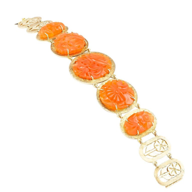 Carved carnelian and yellow gold link bracelet circa 1960.  DETAILS:  GEMSTONES:  five graduating, coin-shaped, carved, and pierced carnelian, semi translucent displaying shades burnt orange and brownish-red color.    METAL:  14-karat yellow
