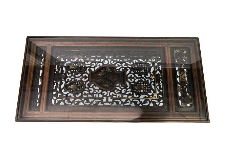 Carved Chinese coffee table is made from a carved Chinese panel with a custom made base. The panel is carved in high relief with gilt highlights. The scene depicts various vases and people figures.