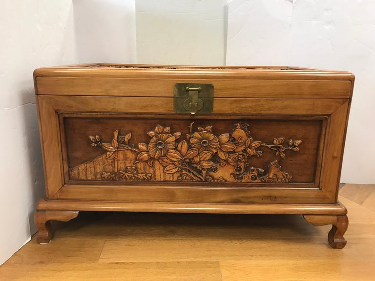 Chinese export trunk features stunning intricate carved scenery of birds and flowers. The different layers of carvings give it a three dimensional effect. Carvings are on front, back, sides and top. Brass closure opens to cedar interior. Use for