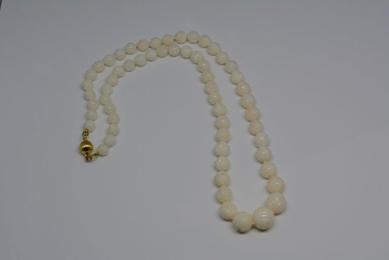 It's not everyday that you come across a nice coral necklace that has beautifully carved beads. The coral is an off-white colour with pink accents on a knotted strand. The carved beads have a bright polish and feel nice to wear against the