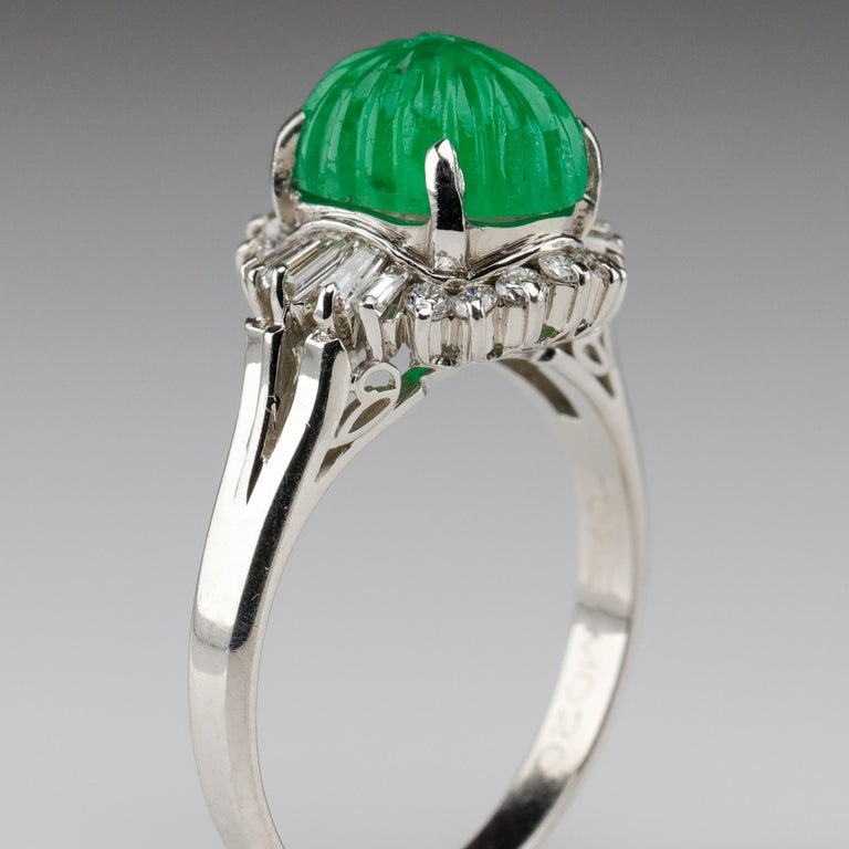 A large gumdrop-green Columbian emerald cabochon has been impeccably carved, set into long and elegant platinum prongs and surrounded by full-cut round and baguette diamonds in this stunning ring from Midcentury Japan. Measuring approximately 10 mm