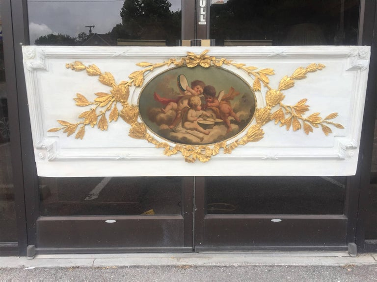 The architectural frieze fragment probably removed from panelling ( Boiserie ). The neoclassical styled panel with leaf garland intertwined with ribbon surrounding a central oil inset of cherubs or putti playing flute, tambourine and drums, probably