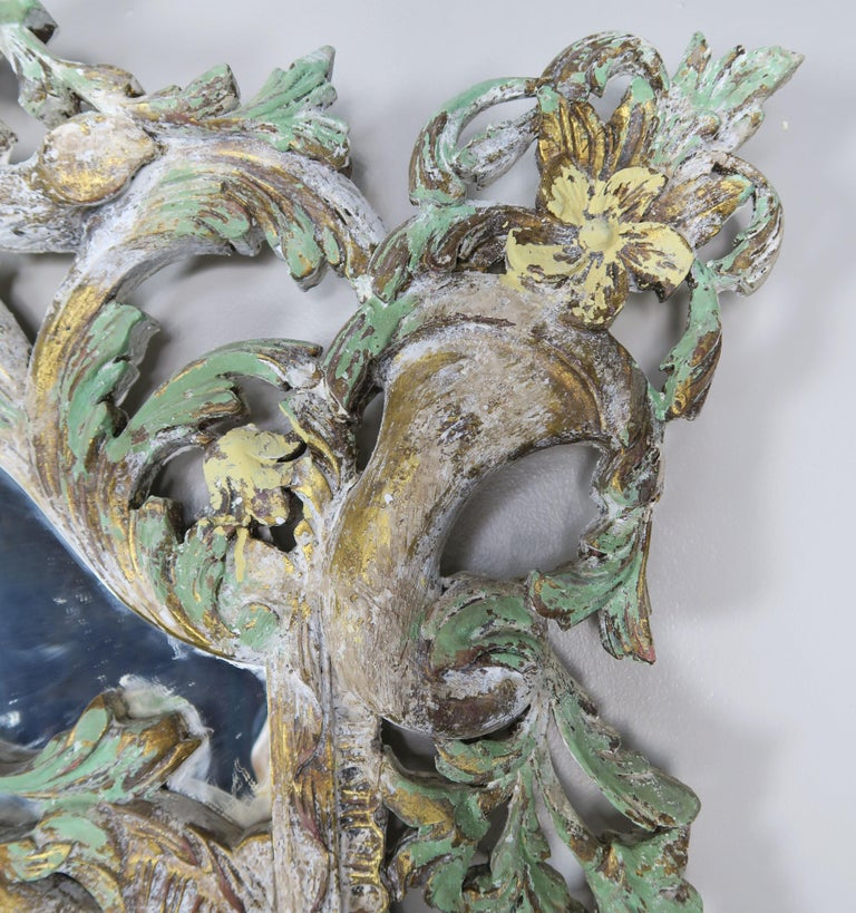 Monumental Italian Rococo style painted mirror with basket of flowers at top and cornucopias in both top corners. Carved garlands of flowers and swirling acanthus leaves throughout the detailed frame. Beautiful shades of antique white, green and