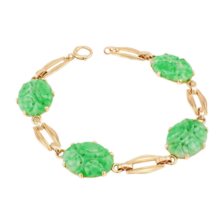 """Carved jadeite and gold link bracelet by Church & Co.  circa 1950.  DETAILS: GEMSTONES:  four oval light green carved jadeites.  METAL:  14-karat yellow gold.  HALLMARKS:  maker's mark for Church & Co.  MEASUREMENTS:  approximately 7 ½"""" (19.0 cm)"""