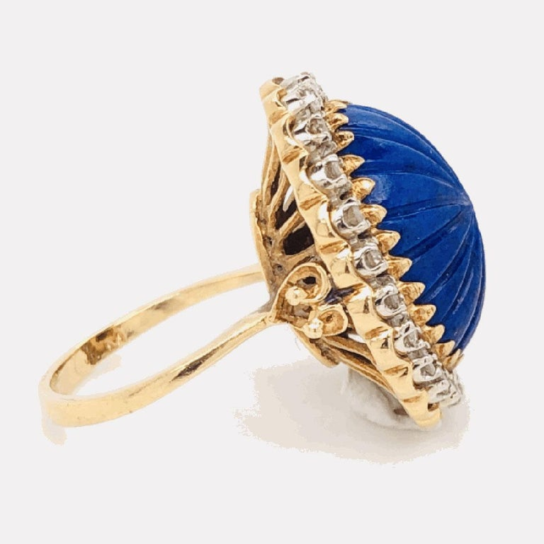 Elegant and finely detailed Lapis Lazuli Cocktail Ring, center set with a Carved Cabochon Lapis Lazuli, bright blue with fabulous tones and small gold flecks, surrounded  with Diamonds weighing  approx. of 0.45 total Carat weight. This beautiful