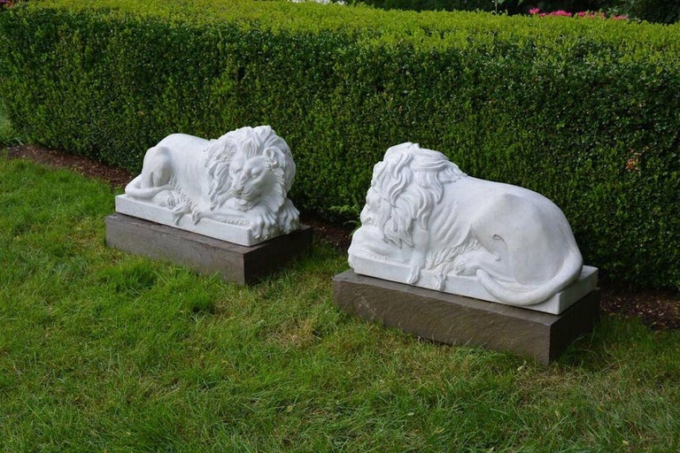 A pair of carved marble lions, inspired by a model by Bertel Thorvaldsen, one lion awake, one asleep with eyes closed, both with clawed front paws extending beyond integral base, Asian, circa 1990. Measures: 19 ins. high, 27 ins. long, 15 ins. wide