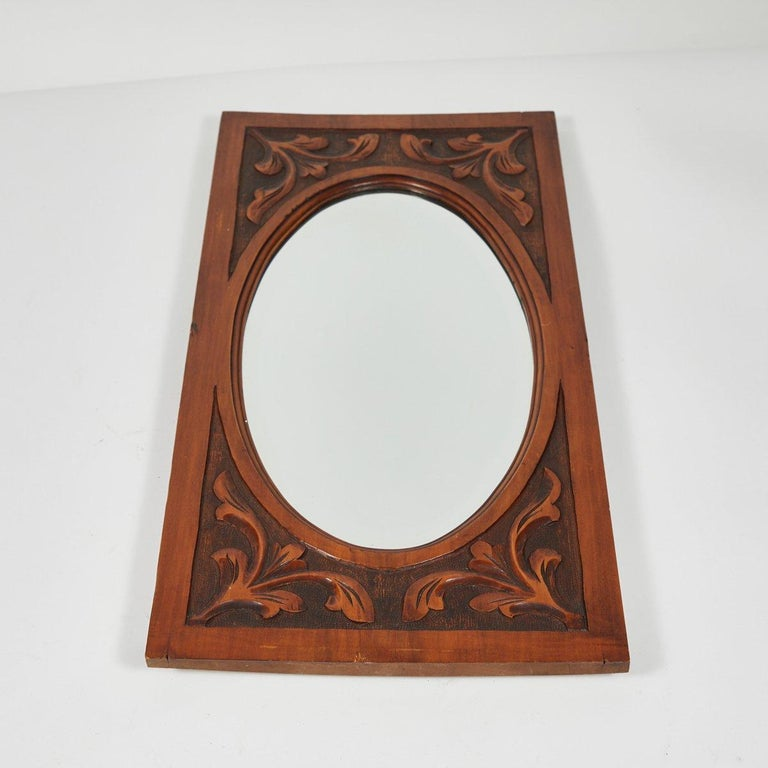 Carved mirror in mahogany with oval beveled glass.