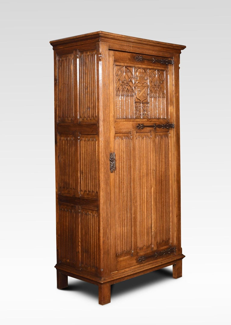 Solid oak wardrobe the moulded cornice above the large door with cast strap hinges Gothic tracery and linenfold decoration. Opening to reveal large hanging area and shelf to the top. All raised up on bracket feet