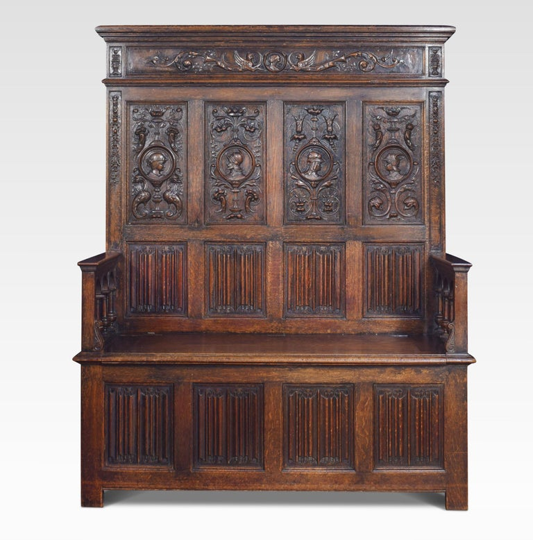 Oak box settle, in the 17th century style, the high back with four panels each centred with a carved knights mask within a moulded roundel, above four linenfold panels, the plain arms raised upon arcaded spindles to the hinged box section and