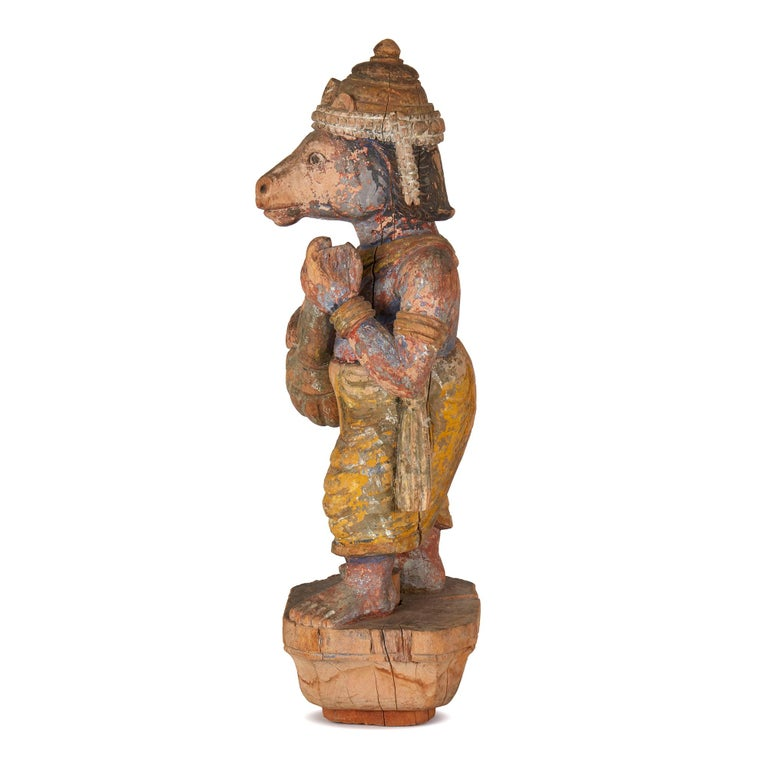 A Fine hand carved antique/vintage Indian wooden figure of an Indian deity with a horse's head and playing a lute like instrument. The figure believed to be a processional mount has original remnants of paint and is mounted on a chip carved wooden